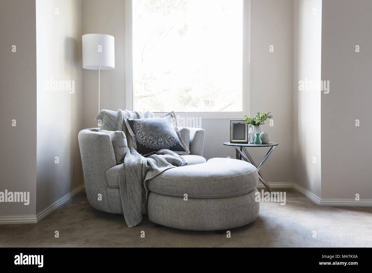 Gorgeous bedroom sofa chair with throw rug and cushion Stock Photo