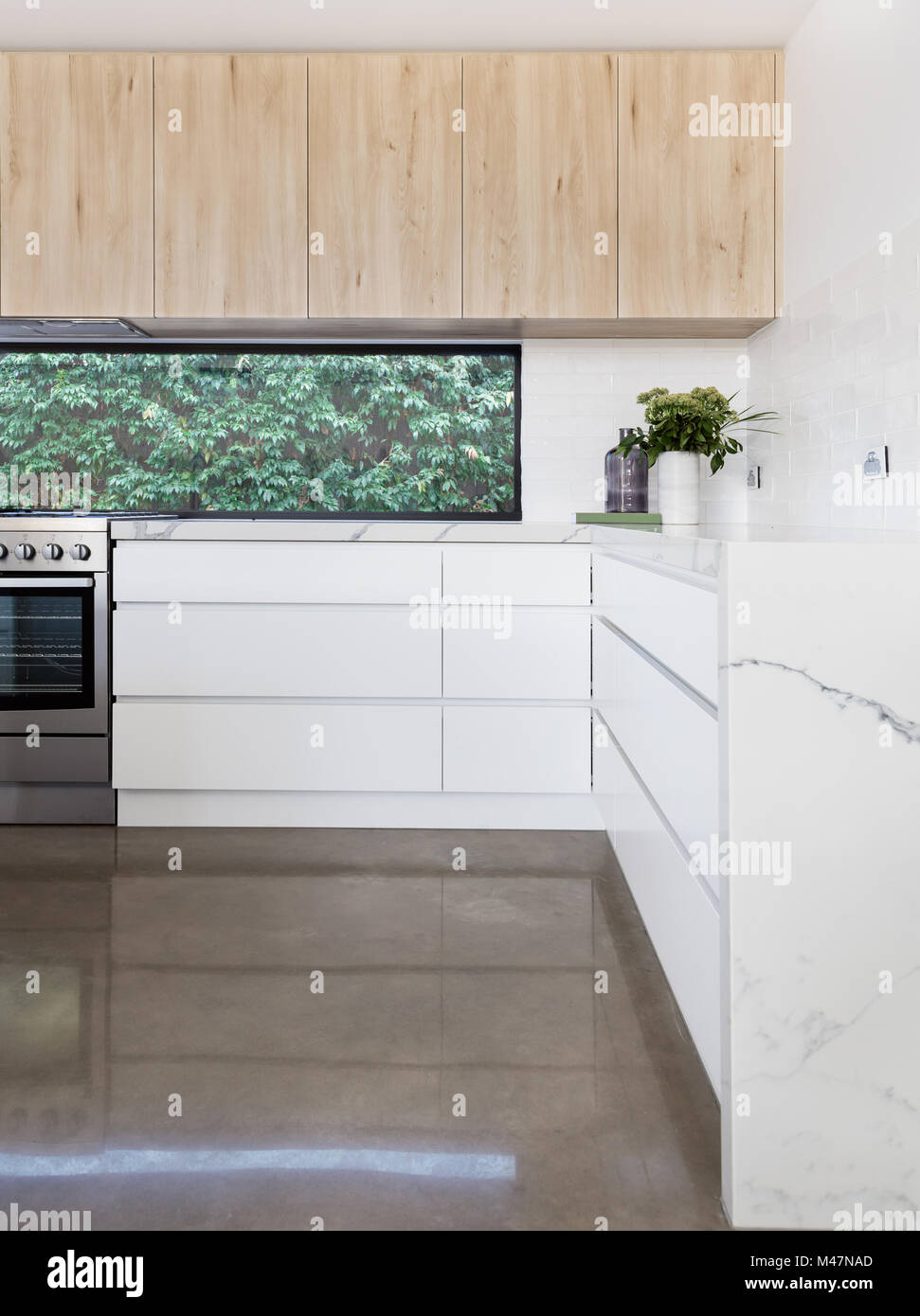 Kitchen details of concrete floor and oversized soft close drawers - Stock Image