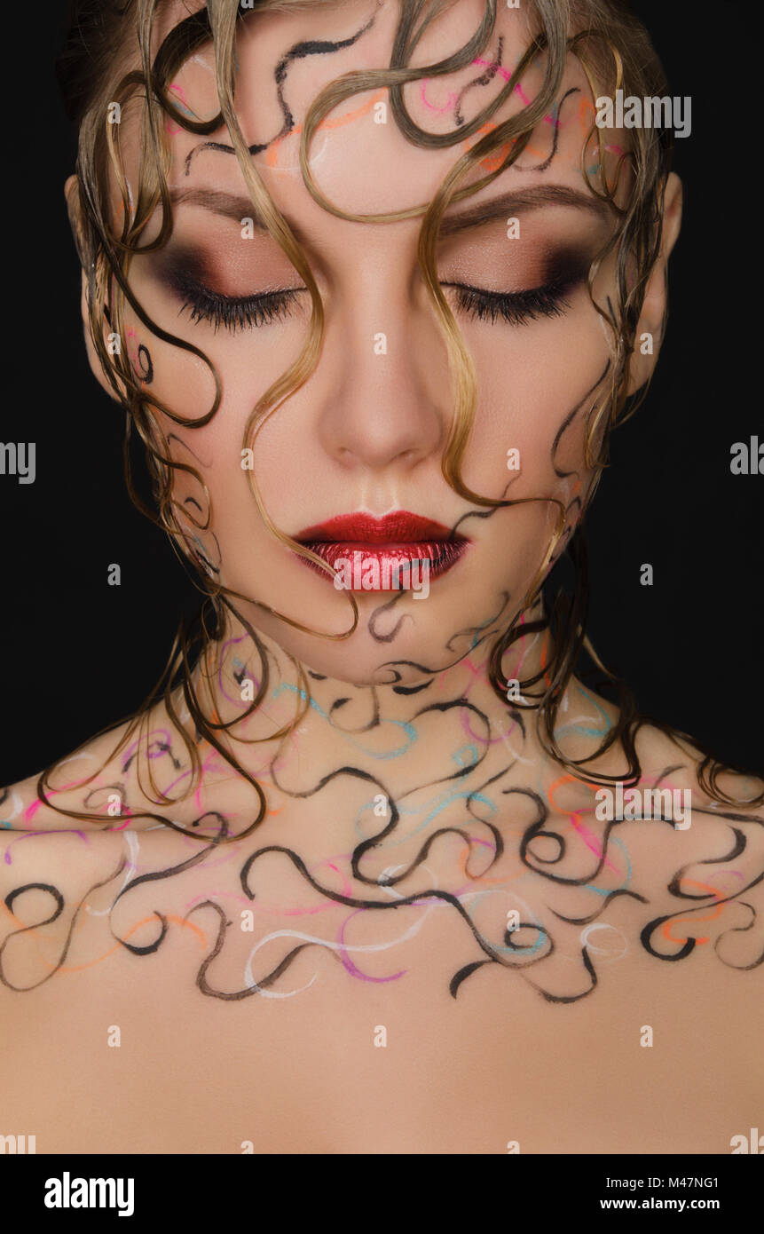 portrait of beautiful woman with wet hair and face art - Stock Image