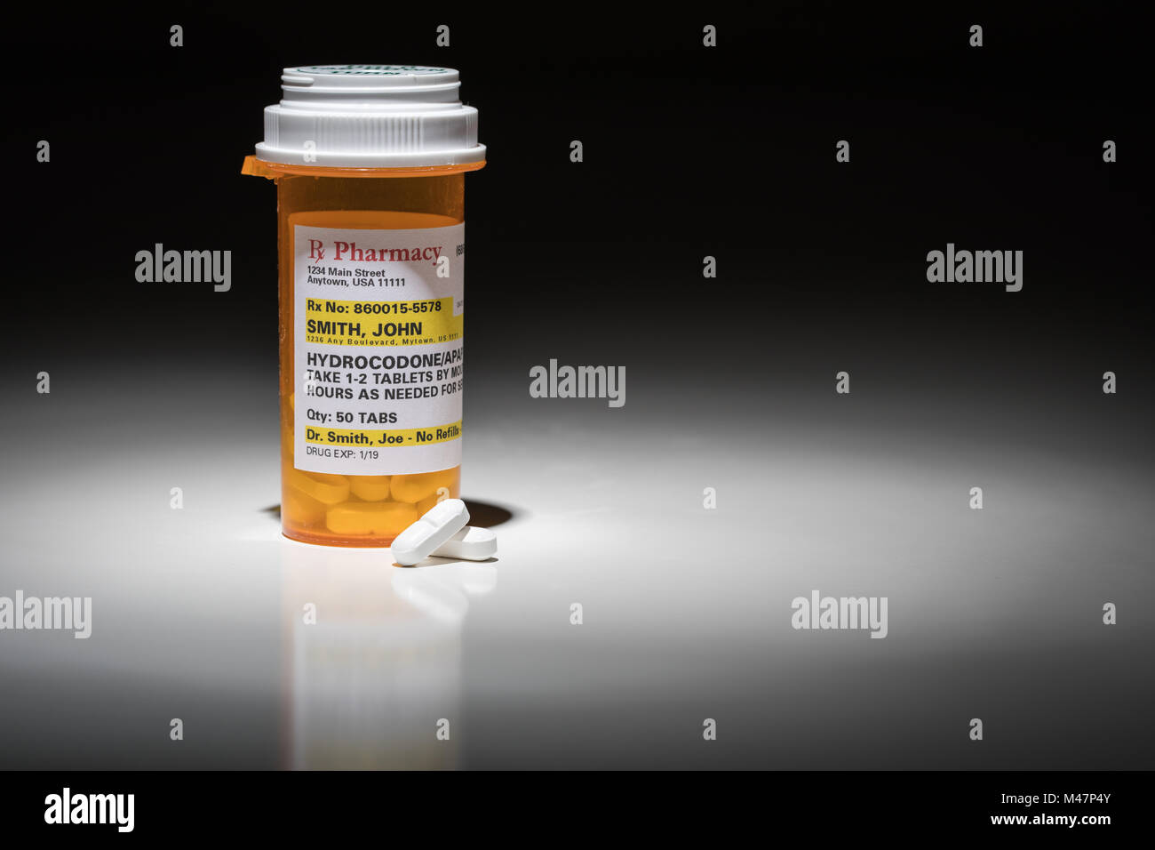 Hydrocodone Pills and Prescription Bottle with Non Proprietary Label. No model release required - contains ficticious - Stock Image