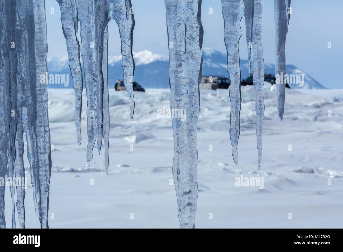Curtain of icicles and tourist expedition on Baikal ice. - Stock Image