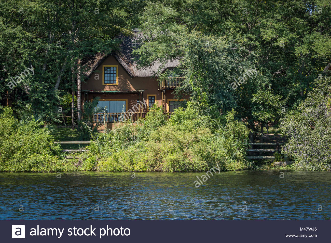 Brown thatched villa in trees on riverbank - Stock Image