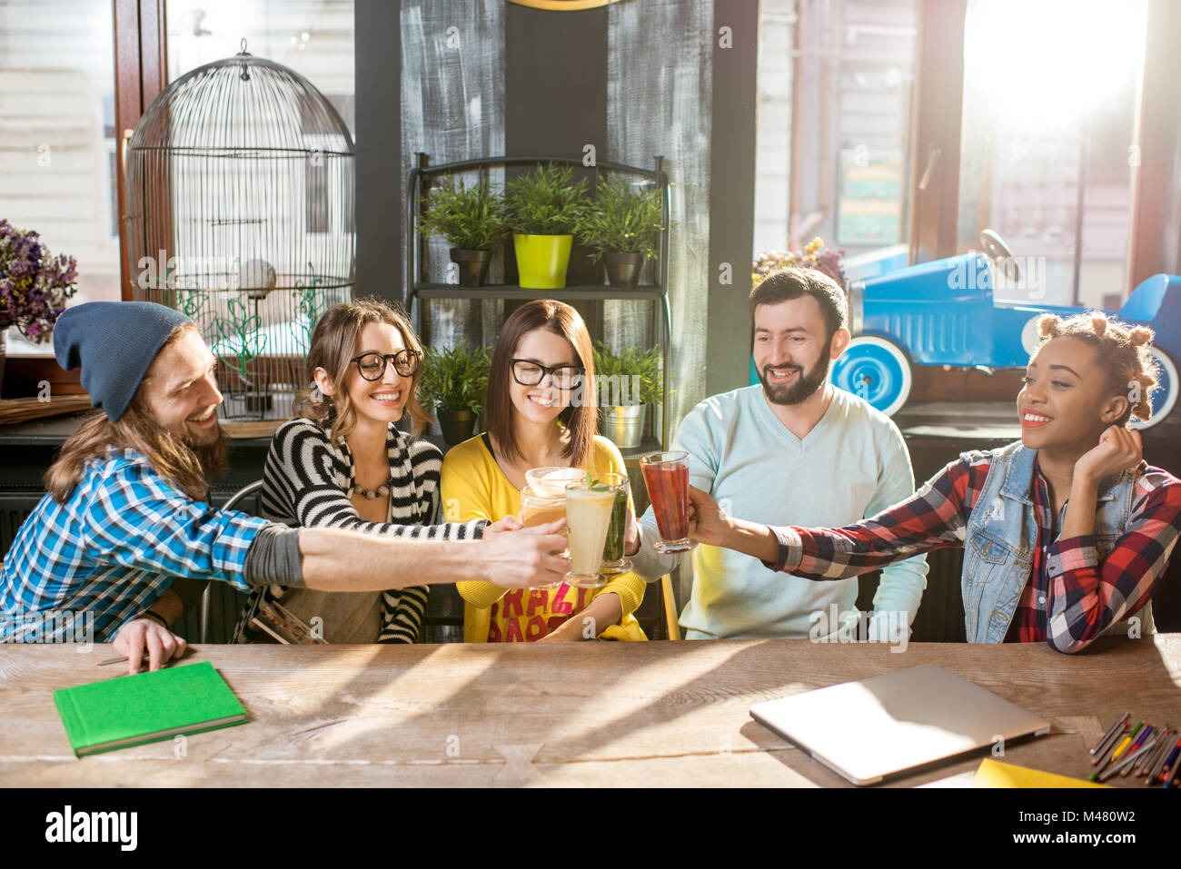 Friends clinking glasses in the modern cafe - Stock Image