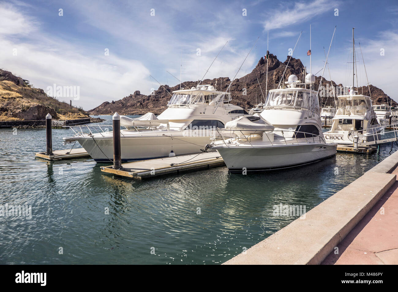 entrance to spacious San Carlos Marina with sleek groomed deep sea fishing pleasure boats moored at outer tiers - Stock Image