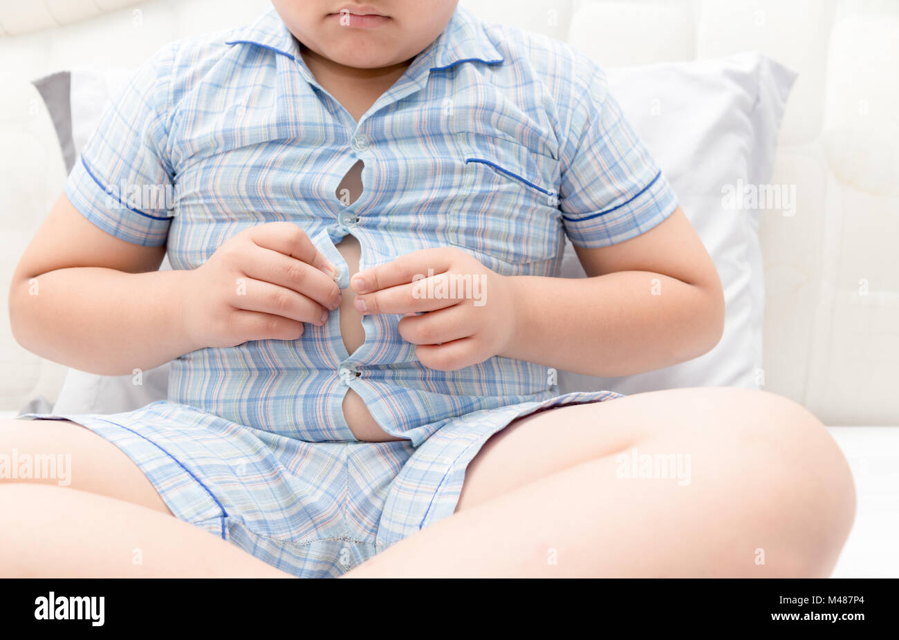 Obese fat boy overweight. Tight shirt of pajamas, healthy concept - Stock Image