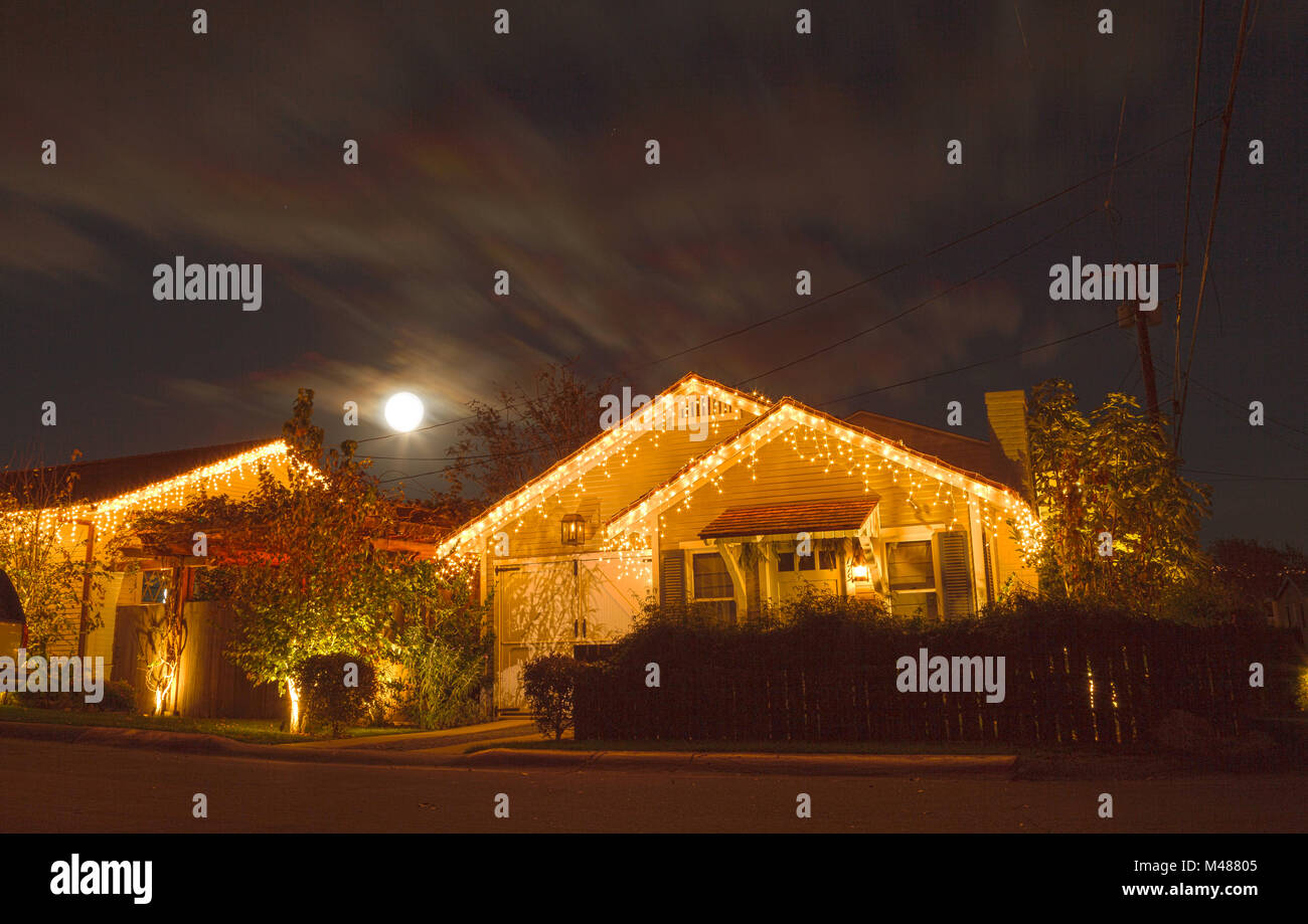 A full moon peaks over a home with Christmas lights - Stock Image