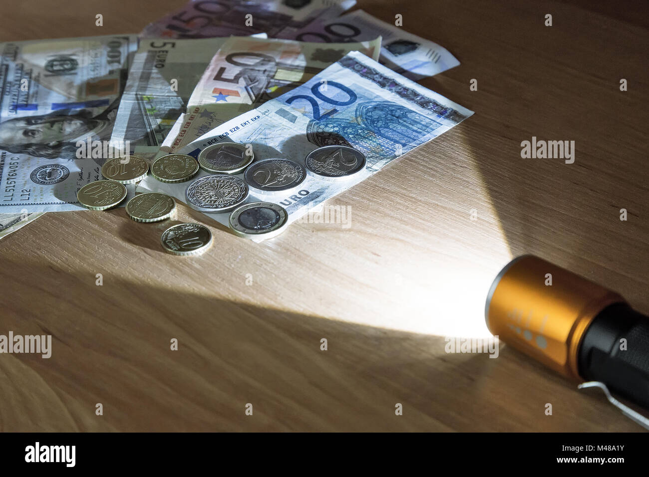 Money in the light beam of the electric torch. - Stock Image