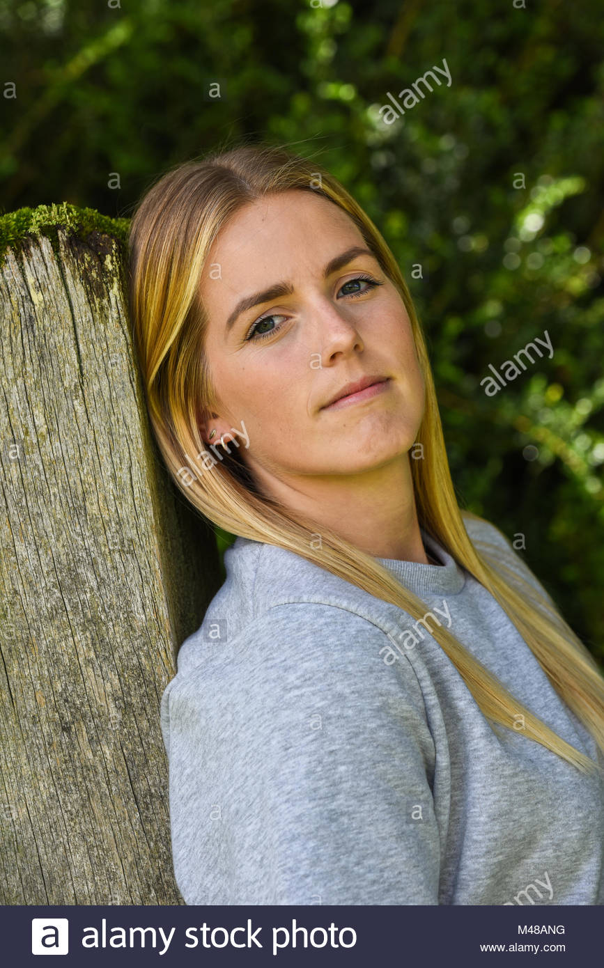 Close-up of blonde leaning against wooden gatepost - Stock Image