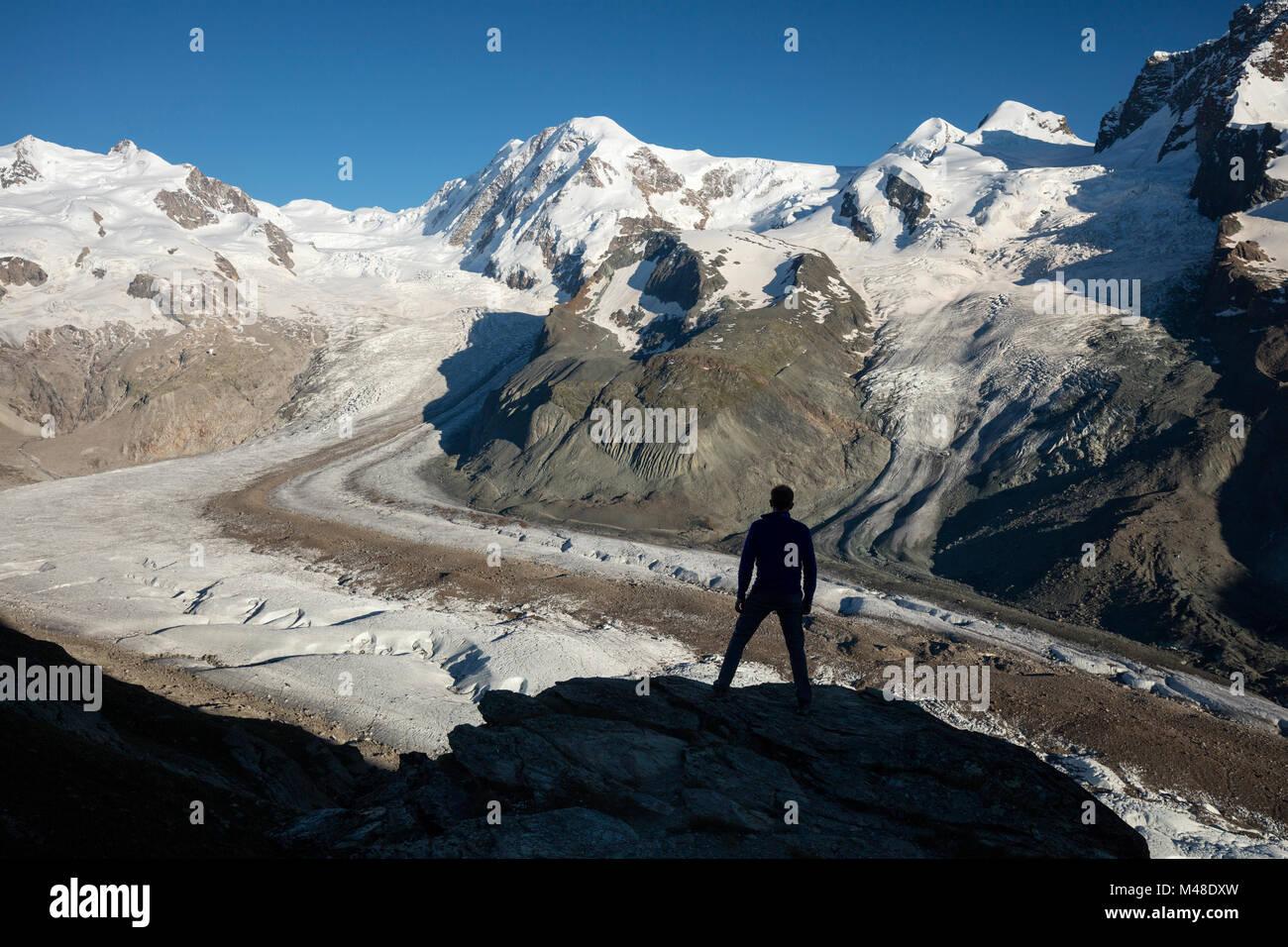 Hiker silhouetted beside Gorner Glacier and Monte Rosa, Gornergrat, Zermatt, Switzerland. - Stock Image