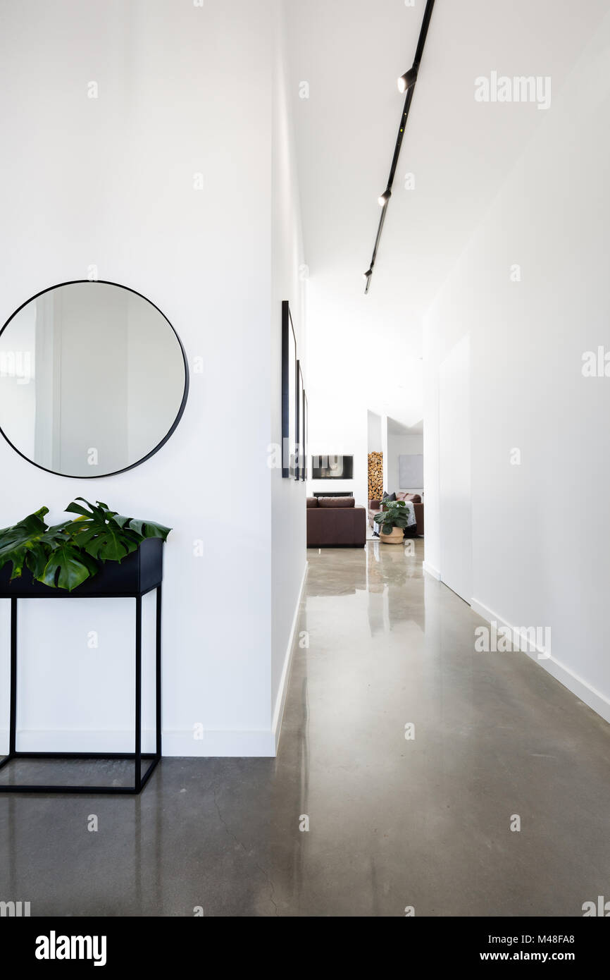 Contemporary new home entry and hallway with polished concrete floors - Stock Image