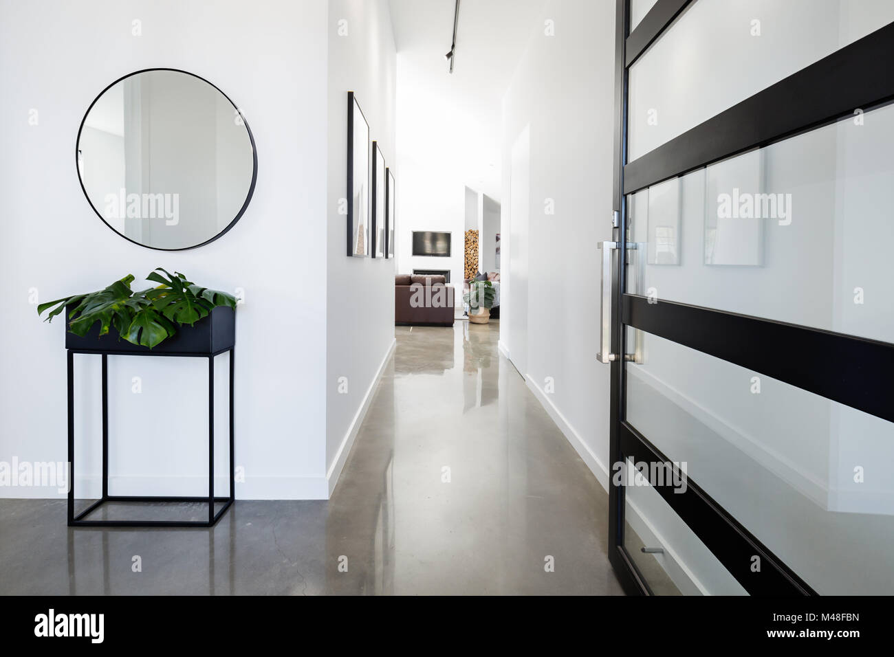 Contemporary home entry hall with polished concrete floors Stock Photo