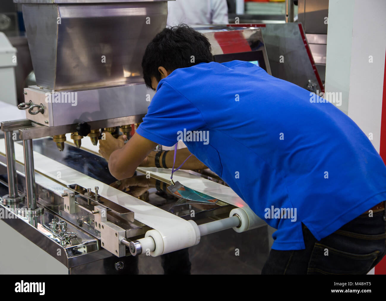 Food worker operate bakery making machine - Stock Image