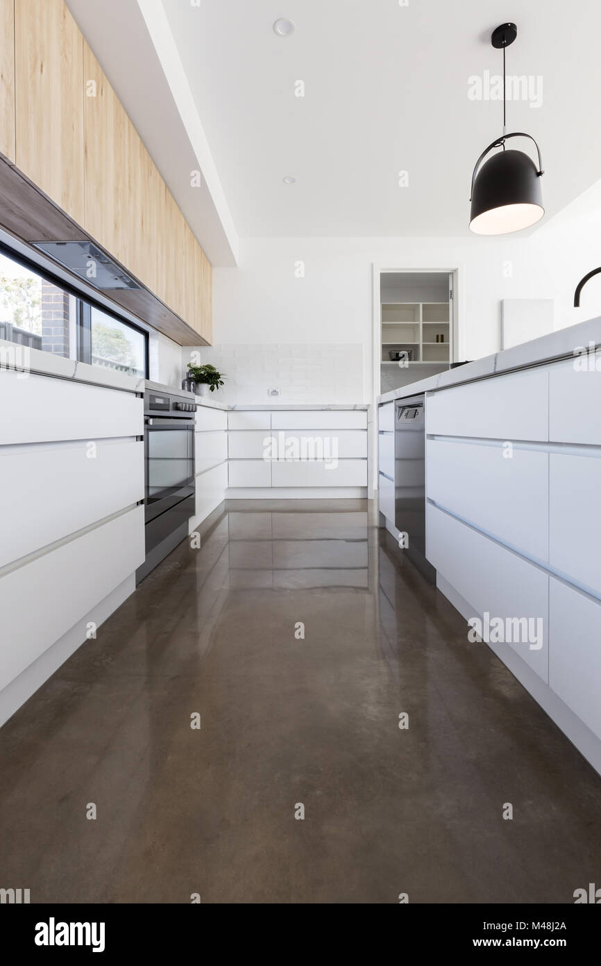 Long galley style kitchen with polished concrete floor - Stock Image