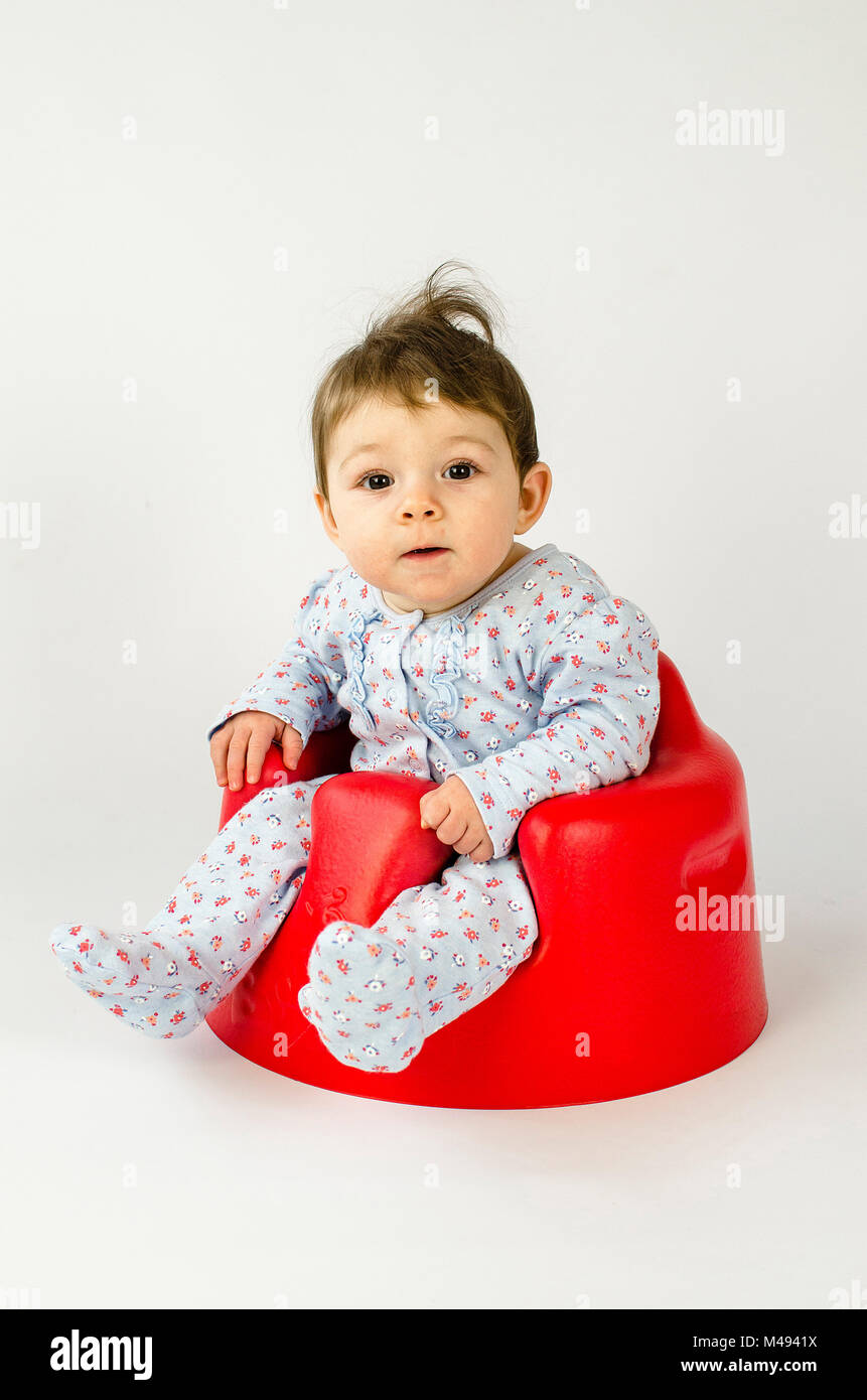 cute baby girl sitting in a plastic seat - Stock Image