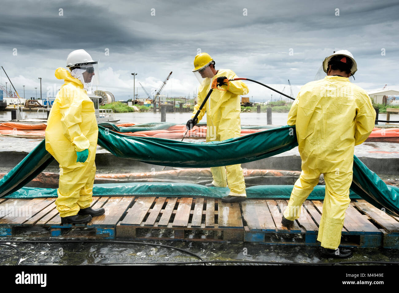 Men cleaning oil containment booms during Deepwater Horizon oil spill, Louisiana, Gulf of Mexico, USA, August 2010 - Stock Image