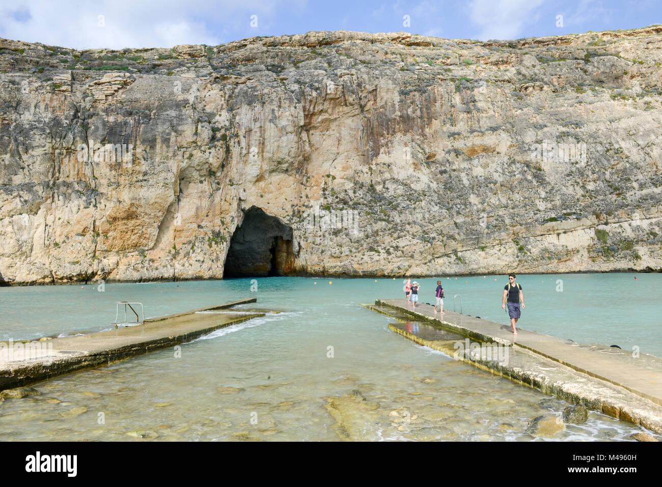 Gozo island, Malta - 30 October 2017: people walking on the pier of inland sea at Gozo Island, Malta. - Stock Image