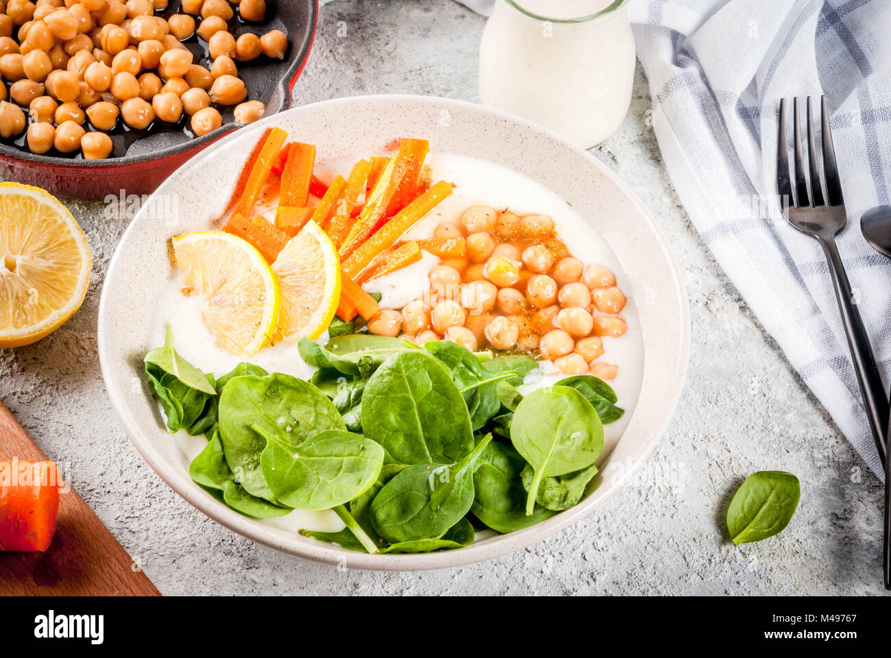 Modern vegan food, savory yogurt bowl with beans, chickpeas, spinach, spicy carrots, lemon, Gray stone background, - Stock Image