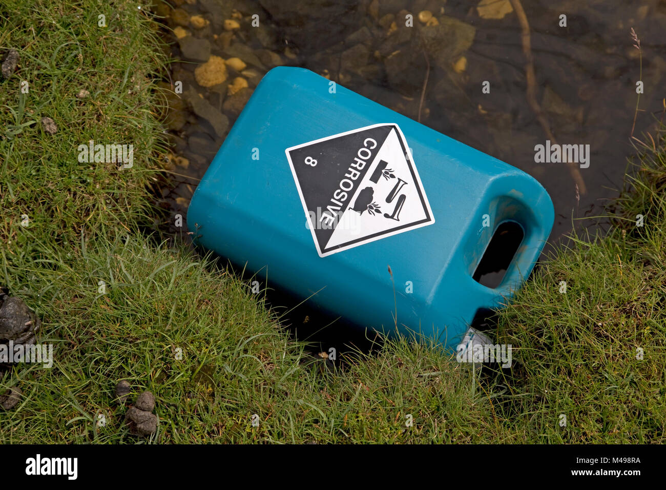 Discarded blue plastic corrosive can in pool on beach Mull Scotland - Stock Image