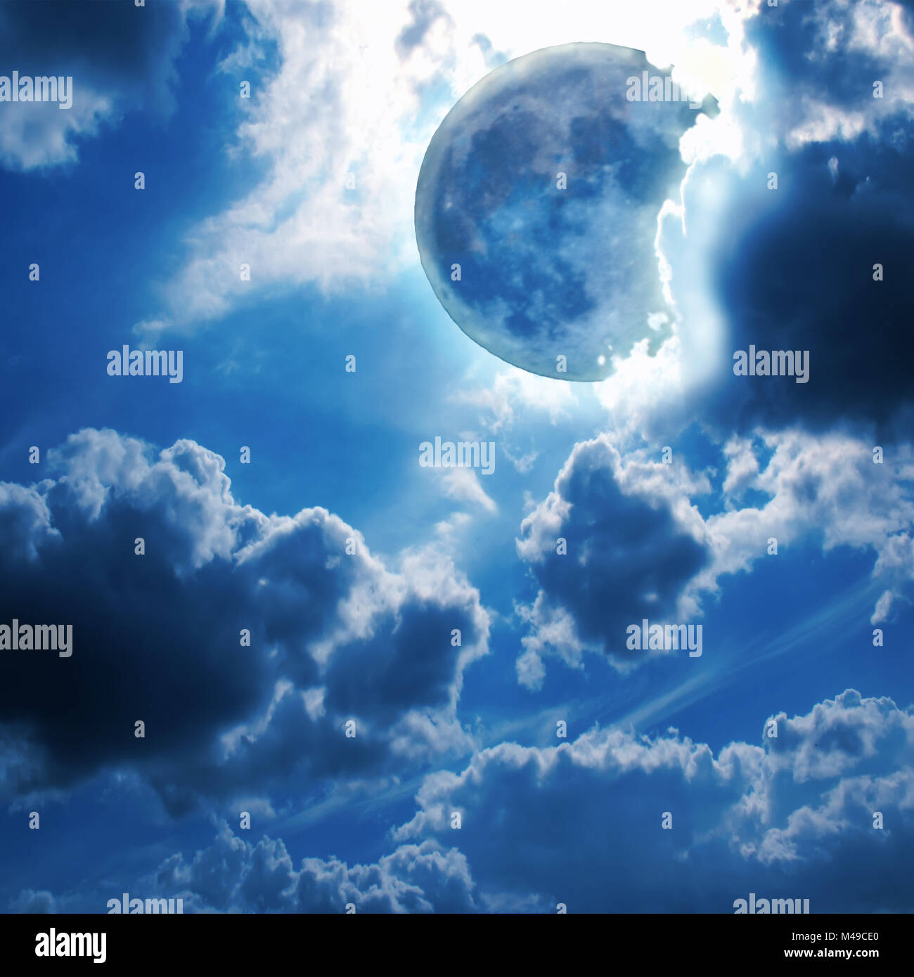 Full moon shines through the clouds in the night sky - Stock Image