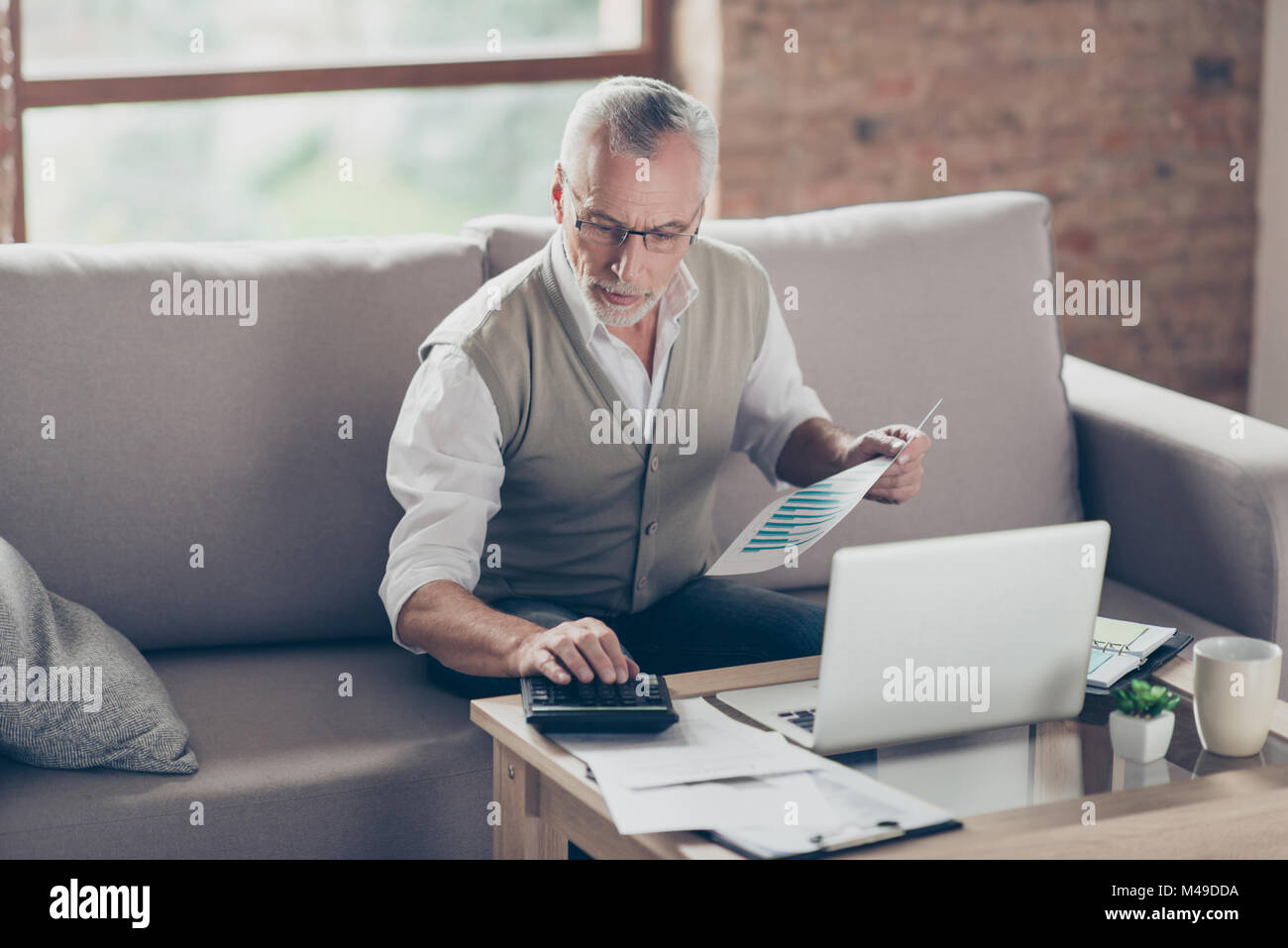 Old confident clever concentrated bearded grandpa is checking his calculations sitting in front of monitor at office - Stock Image