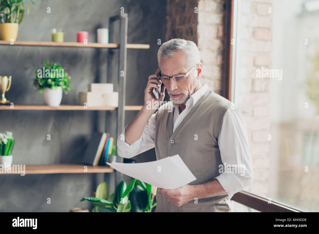 Portrait of elegant experienced old bearded professional successful qualified businessman talking on phone with - Stock Image