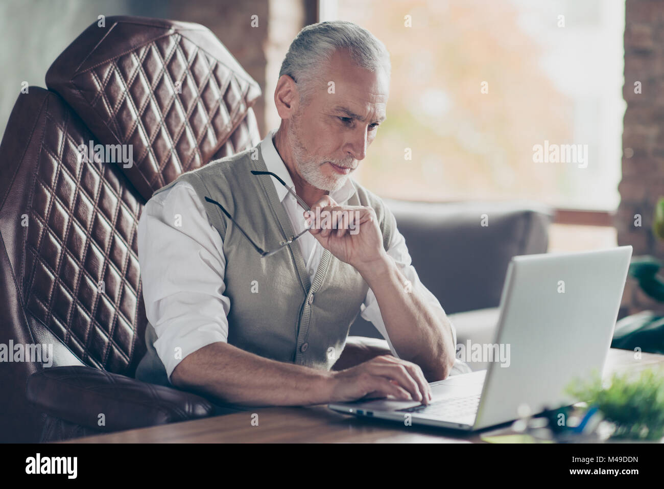 Serious outstanding concentrated respected professional intelligent head of big company wearing waistcoat and white - Stock Image