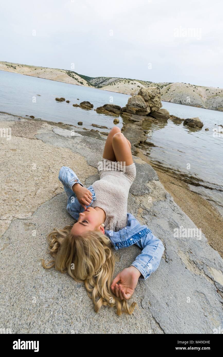 Pretty teen girl lying on back on seaside Stock Photo