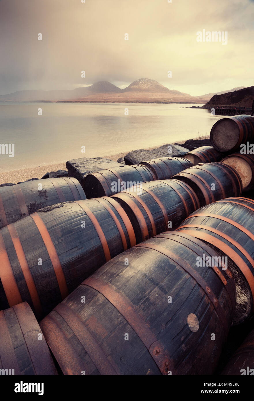 Whisky barrels at Bunnahabhain Distillery looking over to Jura, Islay, Scotland, UK, February. - Stock Image