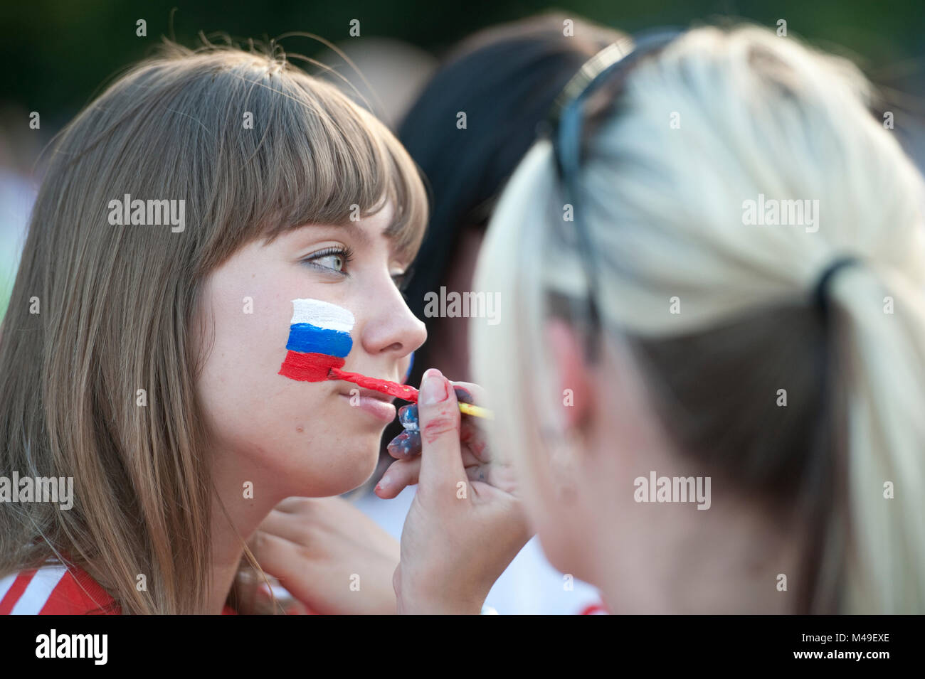 EURO Football 2012. National Stadium, Warsaw. Russia v Greece. Before the match, a Russian fan has her face painted - Stock Image