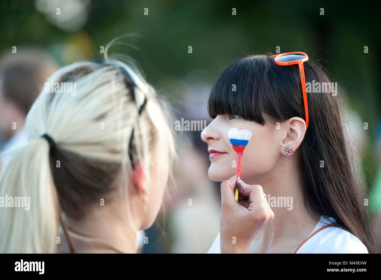 EURO 2012. National Stadium, Warsaw. Russia v Greece. Before match, a Russian fan has her afce painted with russian - Stock Image