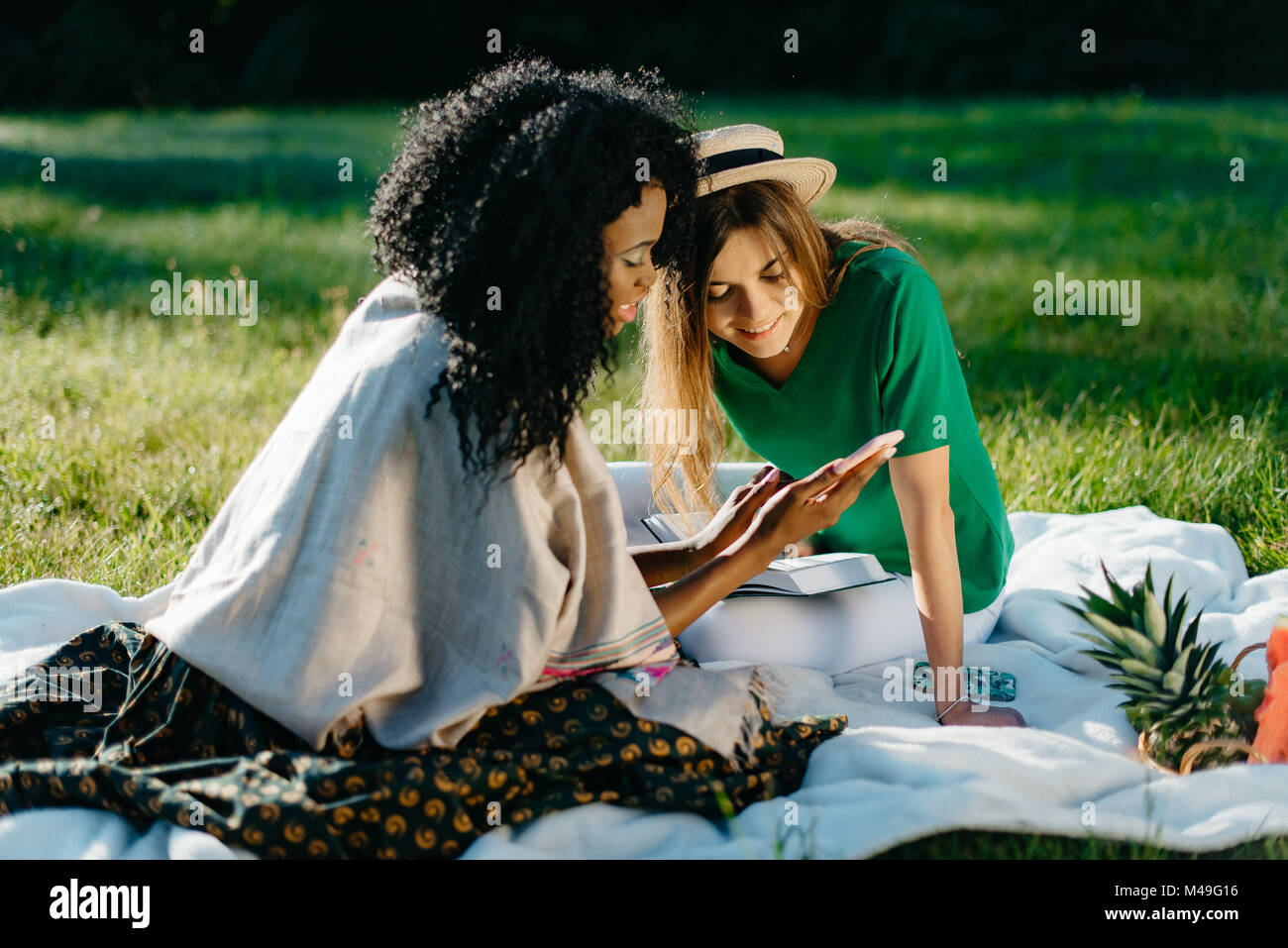 Timespending of two cheerful young attractive girl friends. The adorable african girl is showing something funny - Stock Image