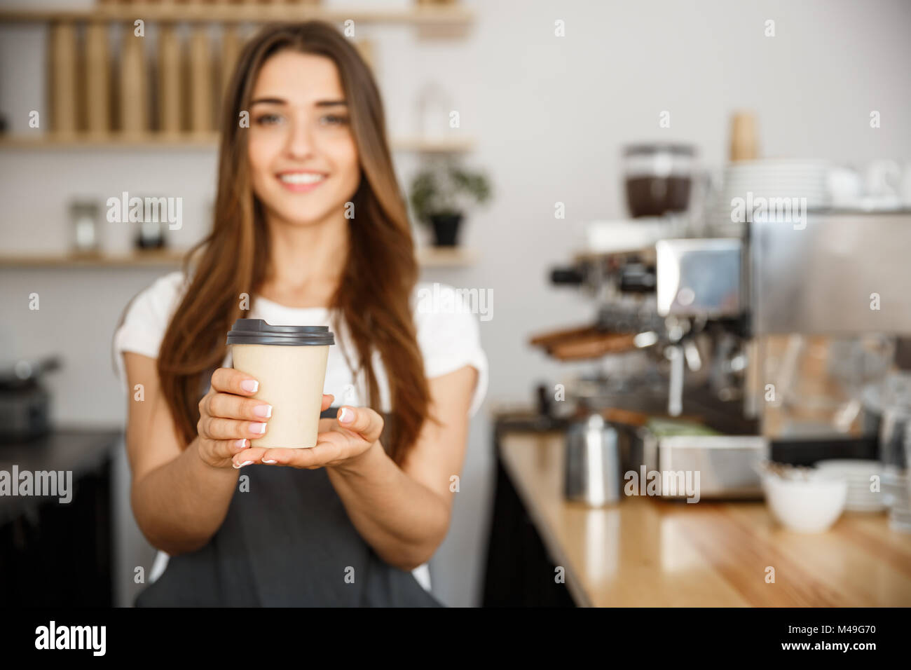Coffee Business Concept - Beautiful Caucasian lady smiling at camera offers disposable take away hot coffee at the - Stock Image