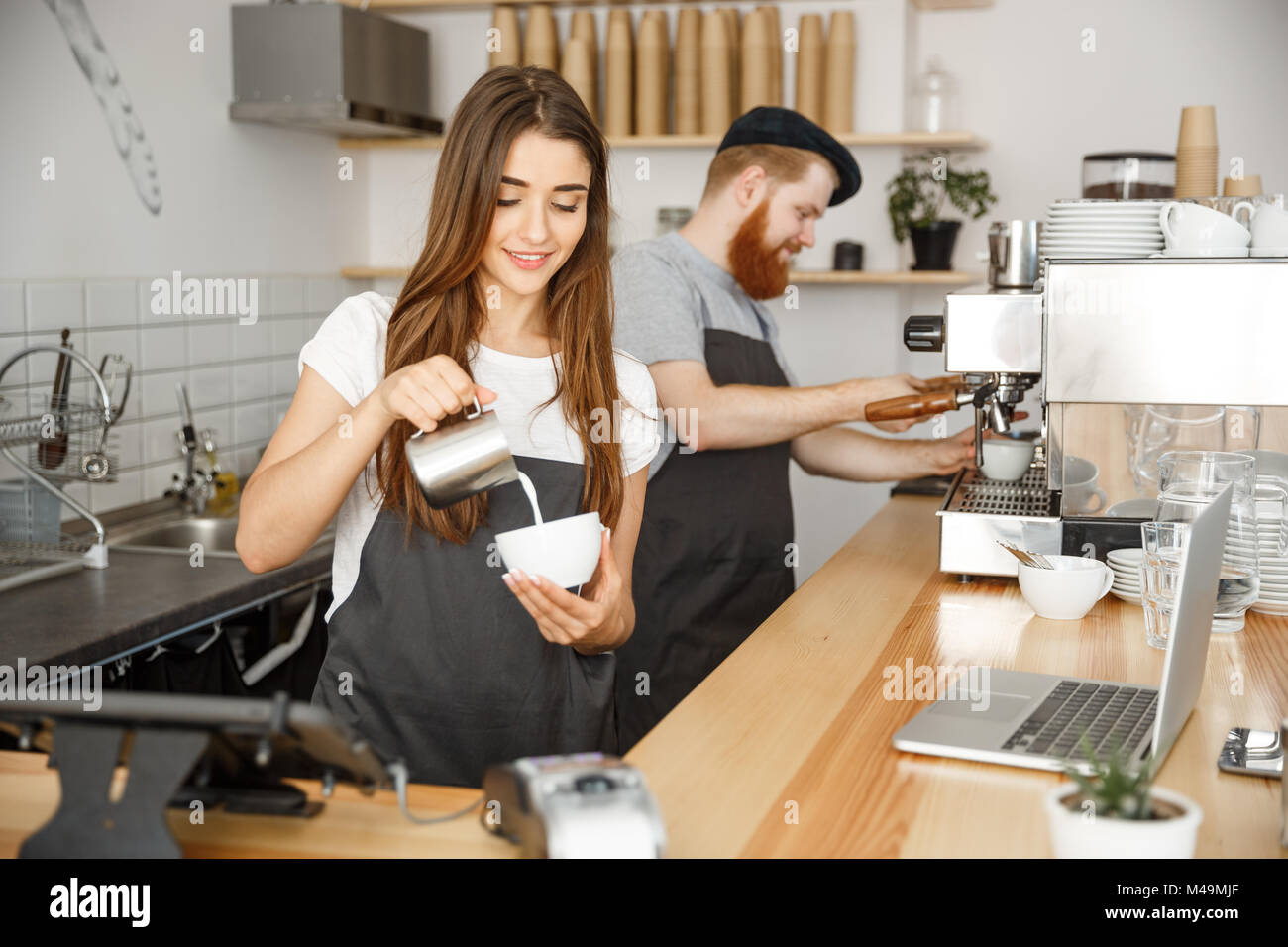 Coffee Business Concept - close-up lady barista in apron preparing and pouring milk into hot cup while standing - Stock Image