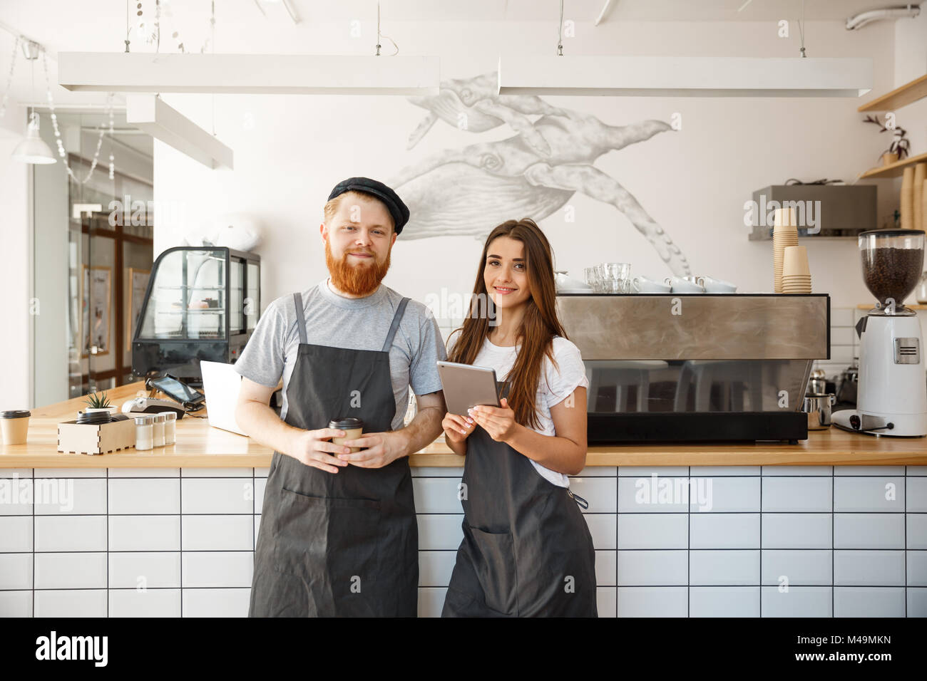 Coffee Business Concept - happy young bartender baristas ready to give service at modern coffee shop. - Stock Image
