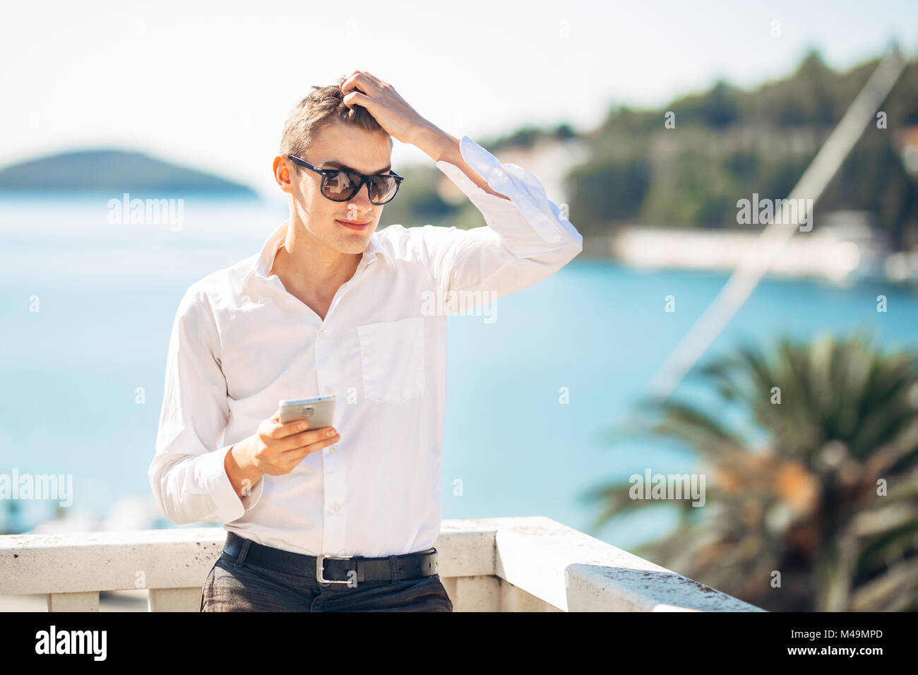Young handsome man enjoying stay at luxury resort hotel with panoramic view on the sea.Smiling cheerful business - Stock Image