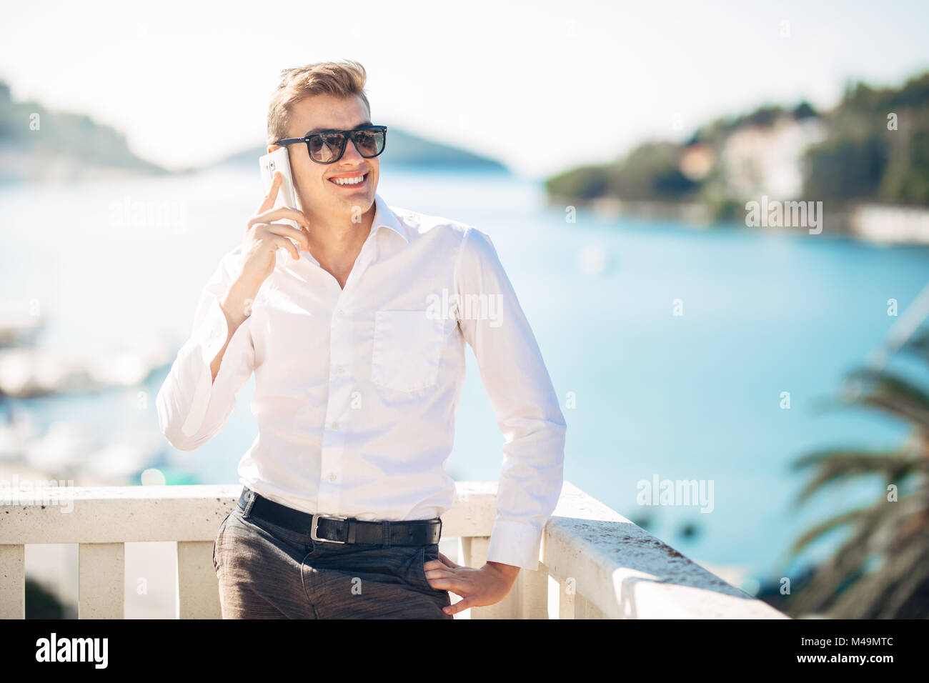 Young handsome man enjoying stay at luxury resort hotel with panoramic view on the sea.Smiling business man using - Stock Image
