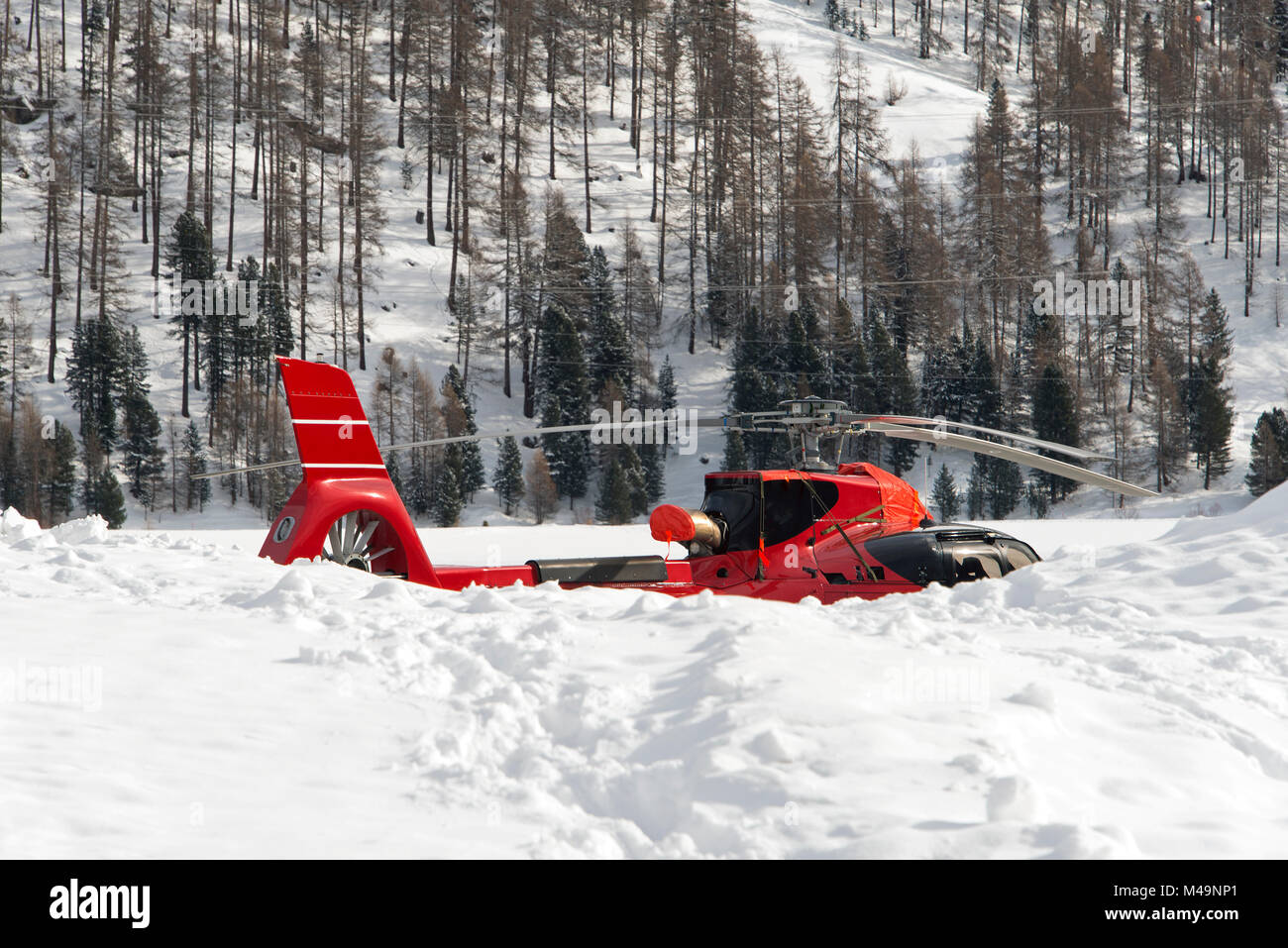 A red airport helicopter in the snow in the alps switzerland - Stock Image