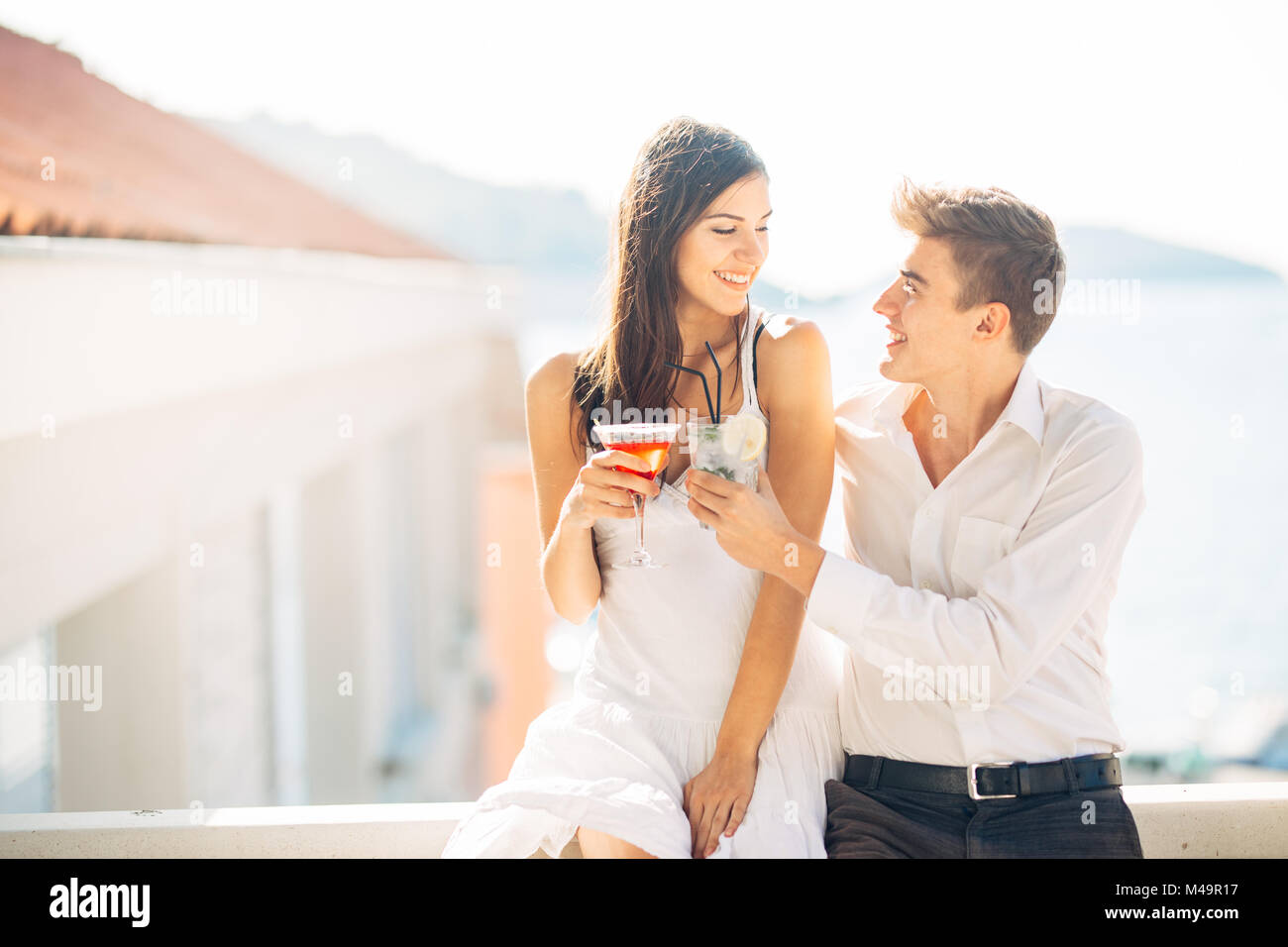 Attractive couple drinking cocktails ,enjoying summer vacation.Smiling,attracted to each other.Flirting and seduction.Man - Stock Image