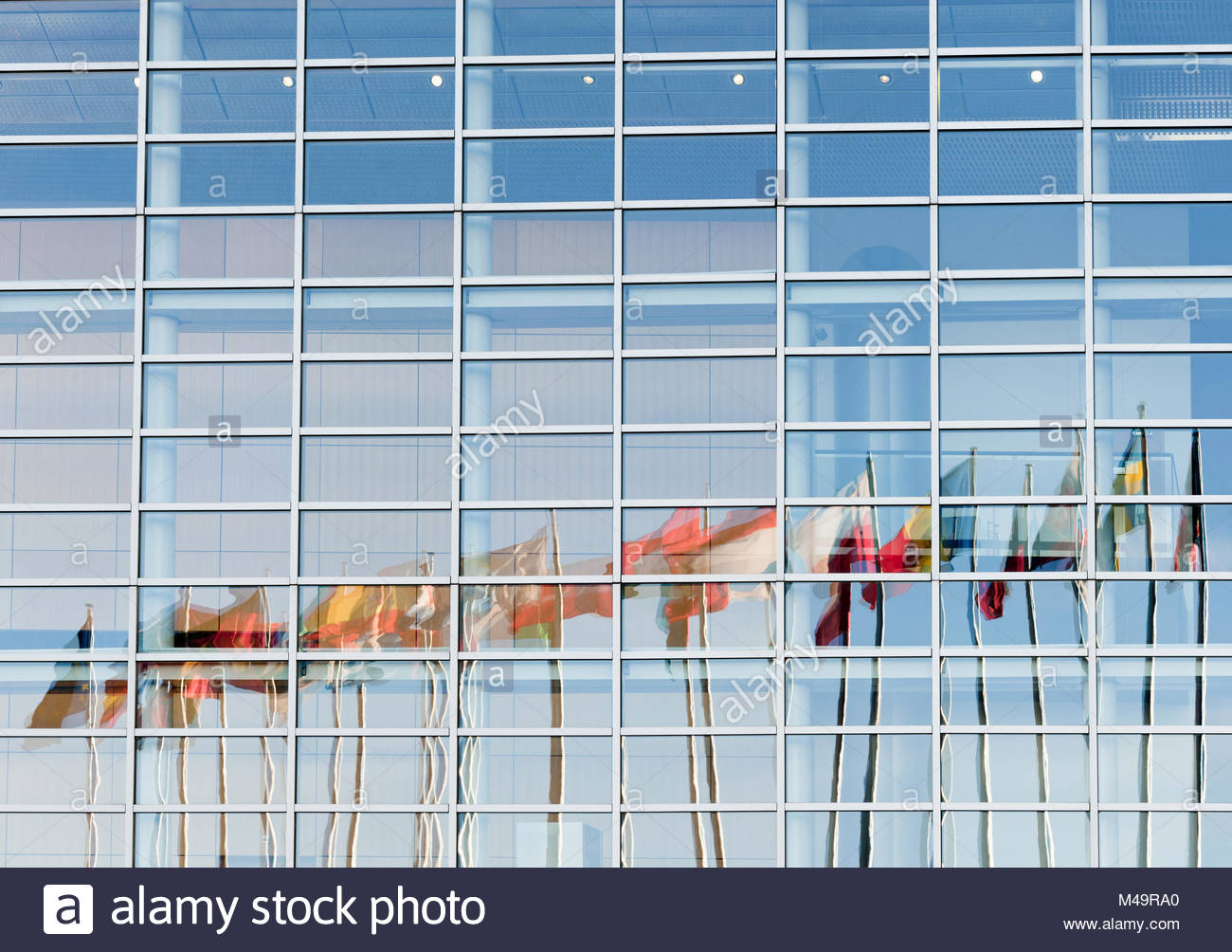 All European Union flags reflected in European Parliament facade - Stock Image