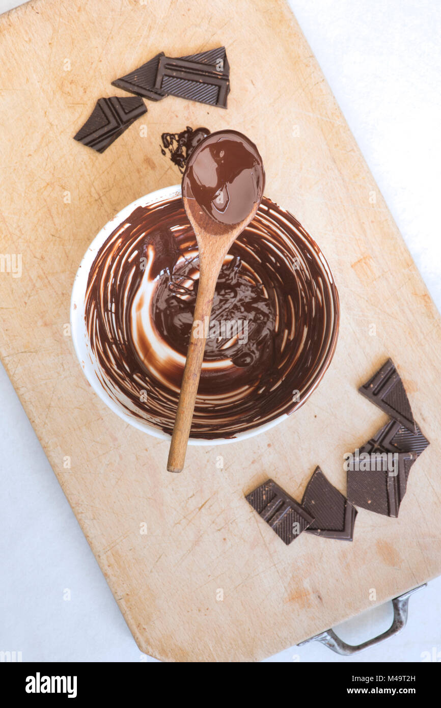 Melted dark chocolate and wooden spoon on a ceramic mixing bowl - Stock Image