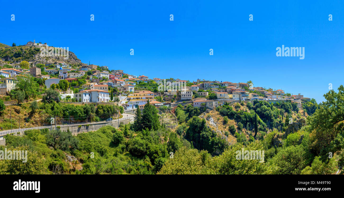 the small Albanian city through which the road runs, located on the mountain overgrown with the wood - Stock Image