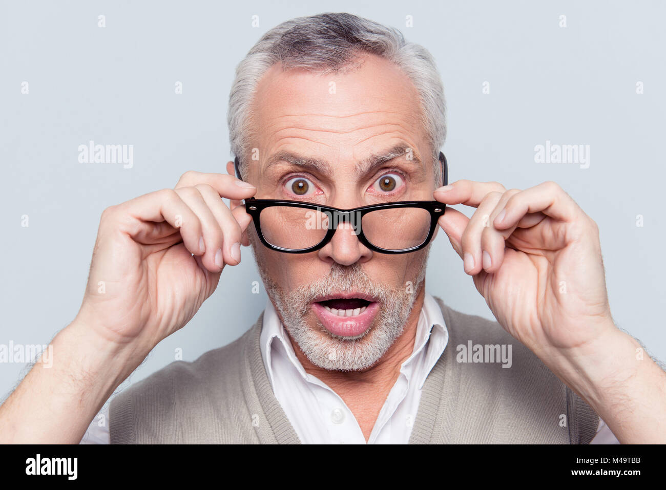 Take off put on glasses. Are you crazy? Close up portrait of shocked surprised uncertain unassured terrified grandfather - Stock Image