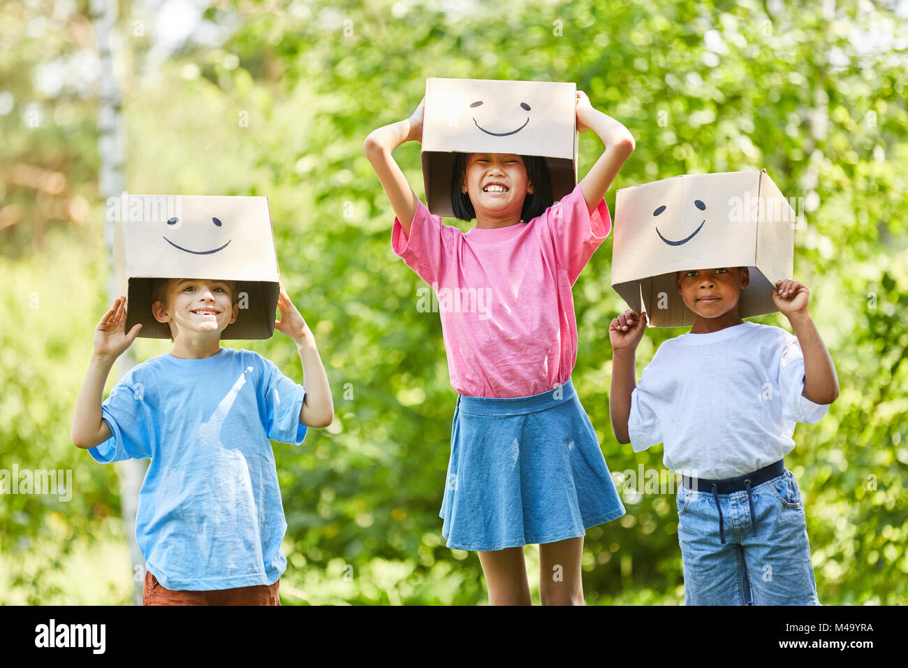 Creative kids play with funny cardboard boxes on their heads in nature - Stock Image
