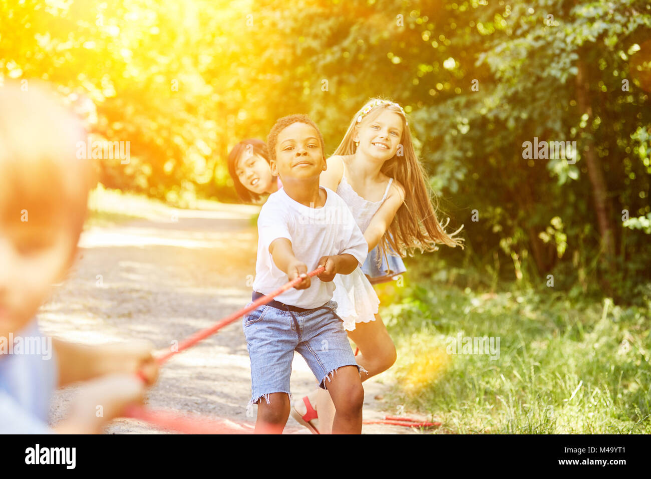 Group of children in tug of war as a team at childrens birthday party in summer - Stock Image
