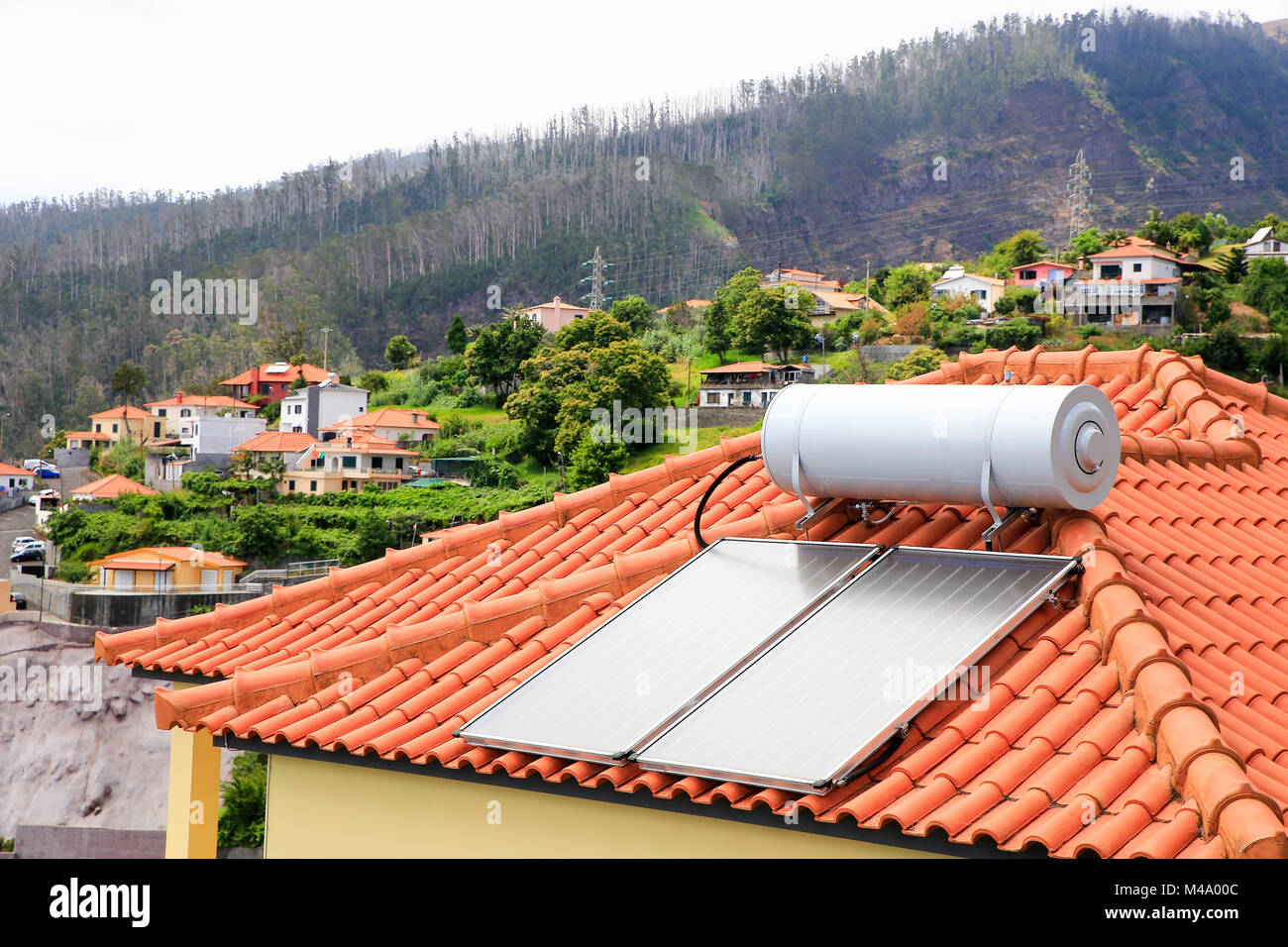 Water boiler with solar panels on roof of house - Stock Image
