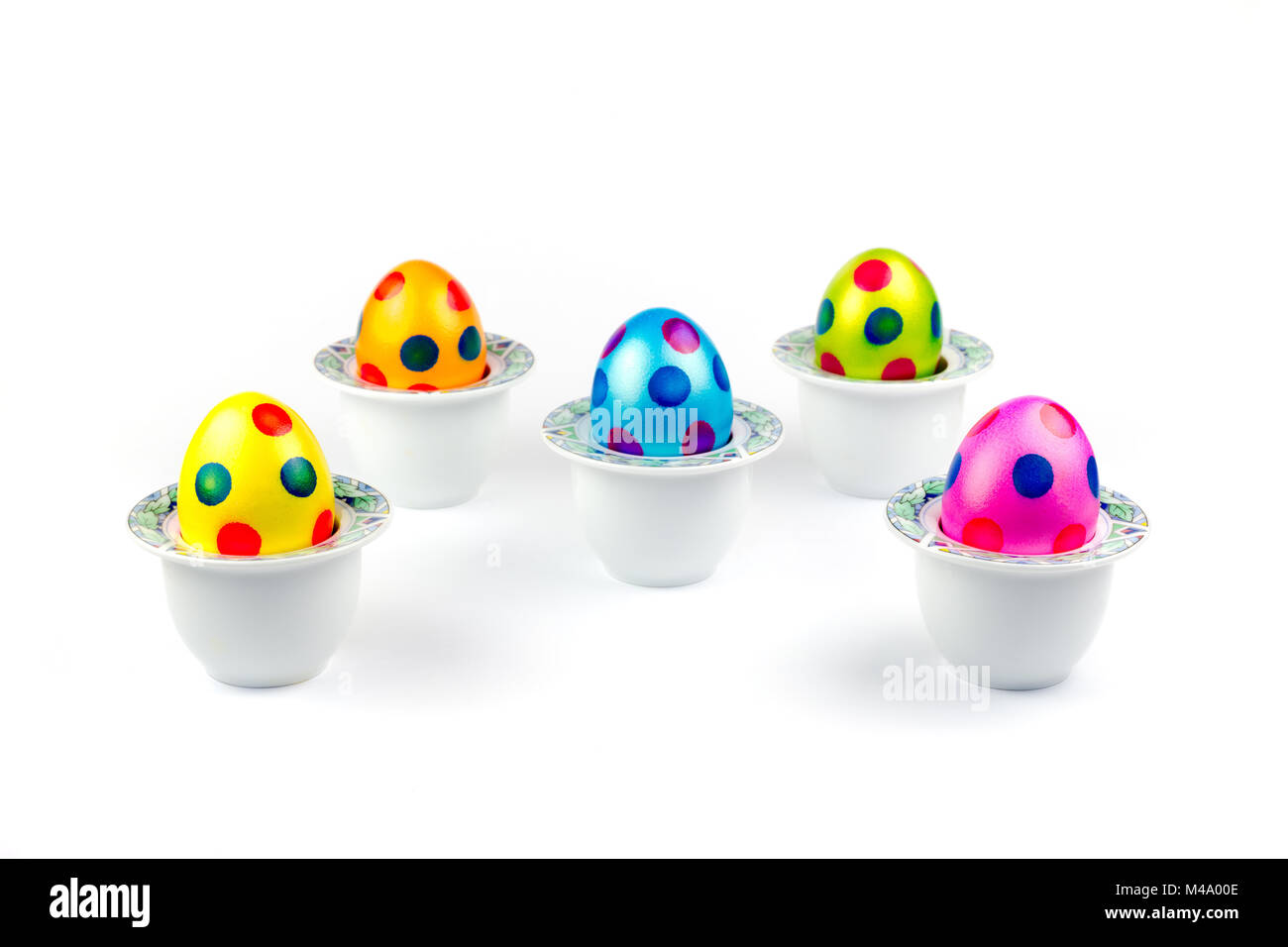 Painted easter eggs standing in porcelain egg cups on white Stock Photo