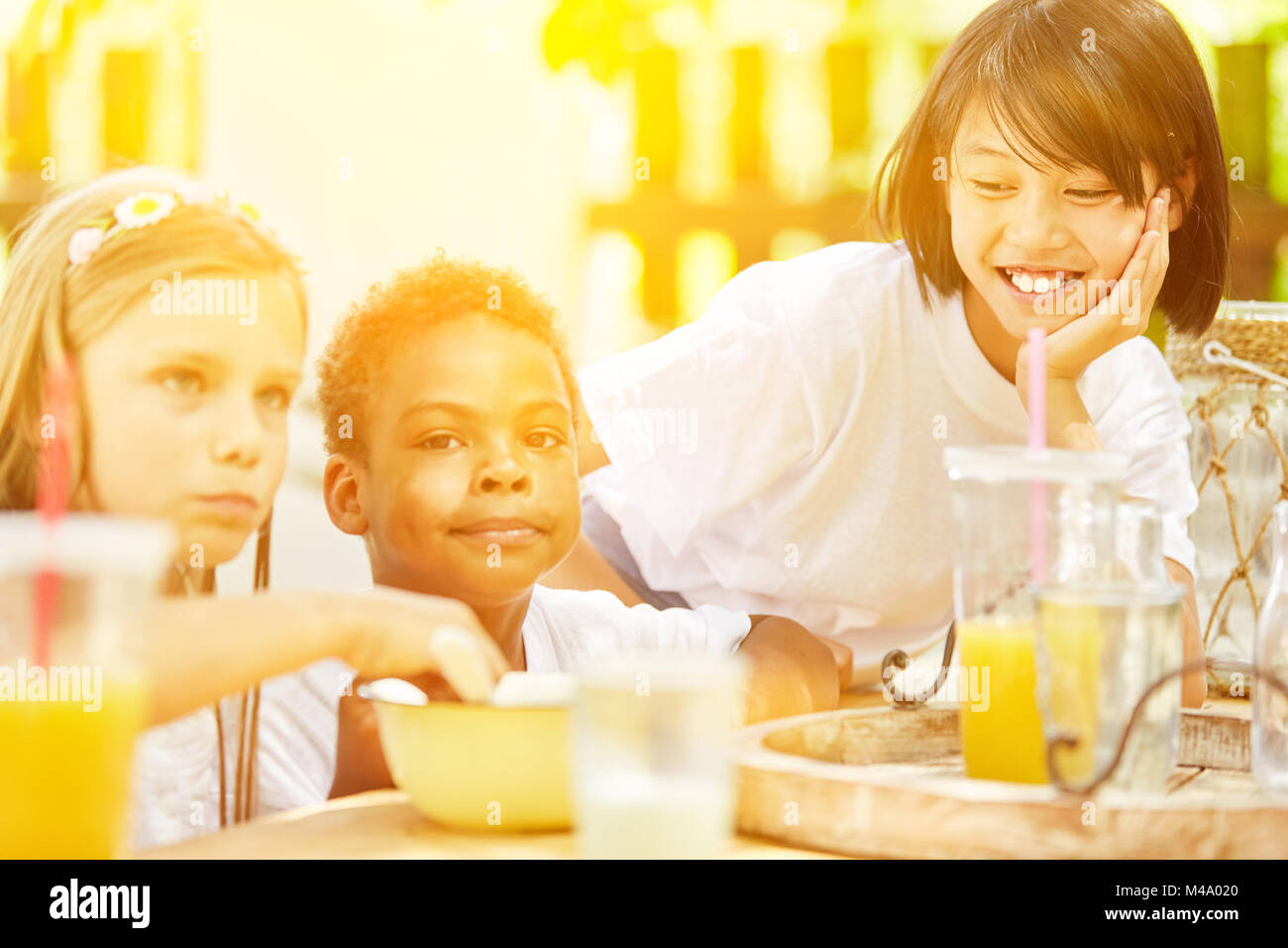 Happy kids eating breakfast cereal together at summer camp - Stock Image
