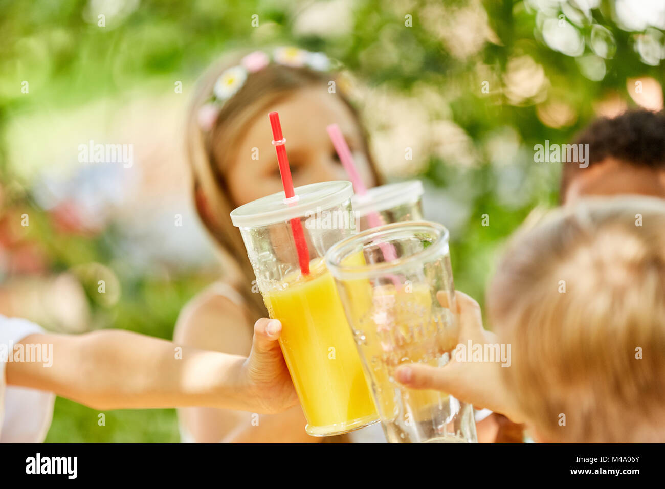 Kids celebrate and toast with juice on a kids birthday or party - Stock Image