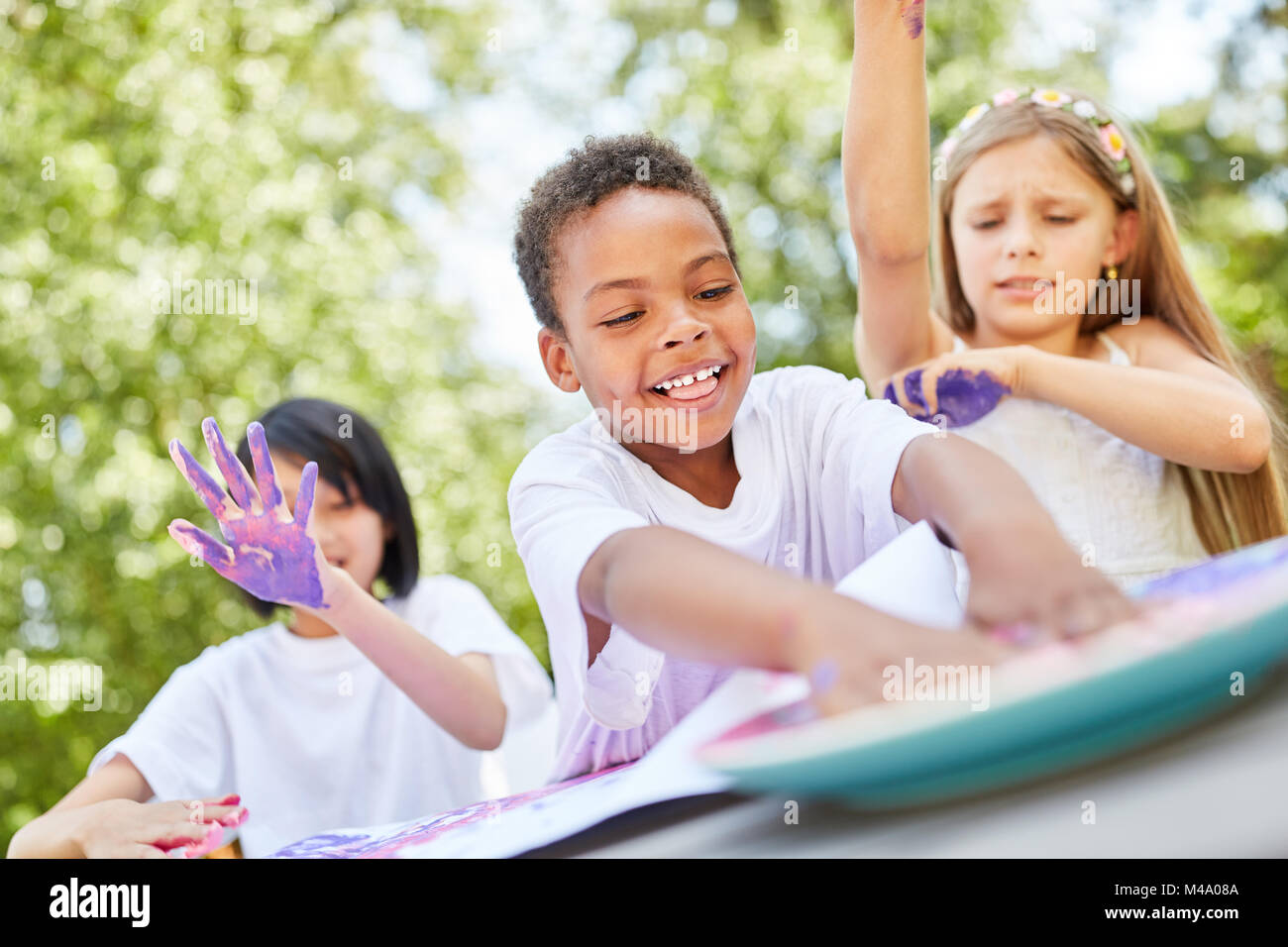 African boy plays and paints with finger paints with his friends - Stock Image