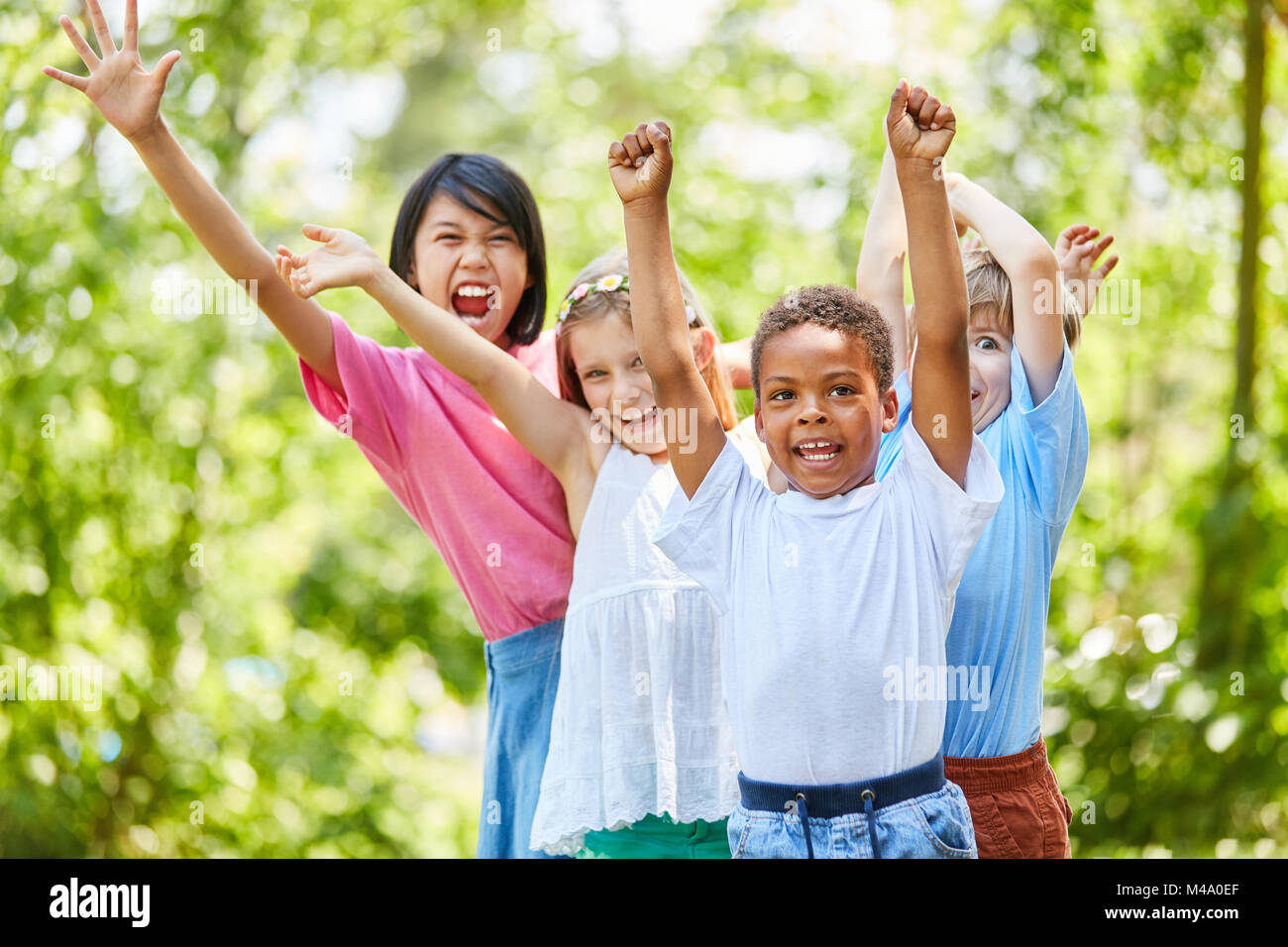 Multicultural group of children enthusiastically cheers on a children's birthday party - Stock Image